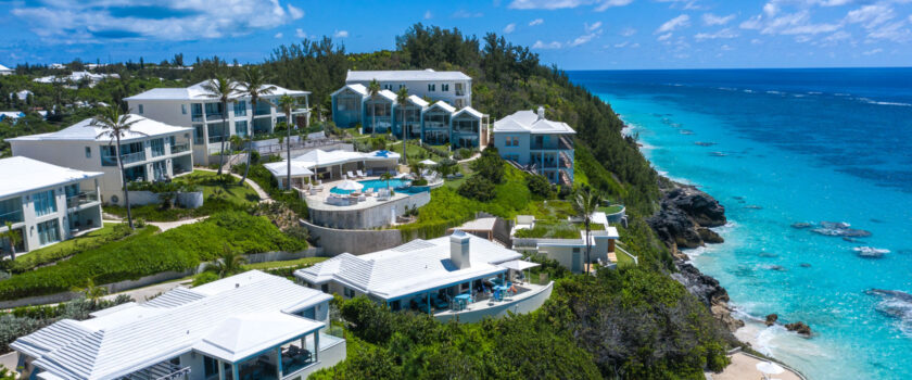 An aerial view of a resort on a large cliff overlooking the ocean.