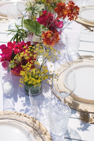 Pink and yellow flowers displayed on a dining table.
