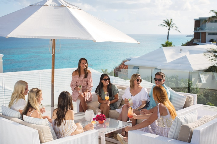 A group of people sitting in an outdoor dining area overlooking the ocean.