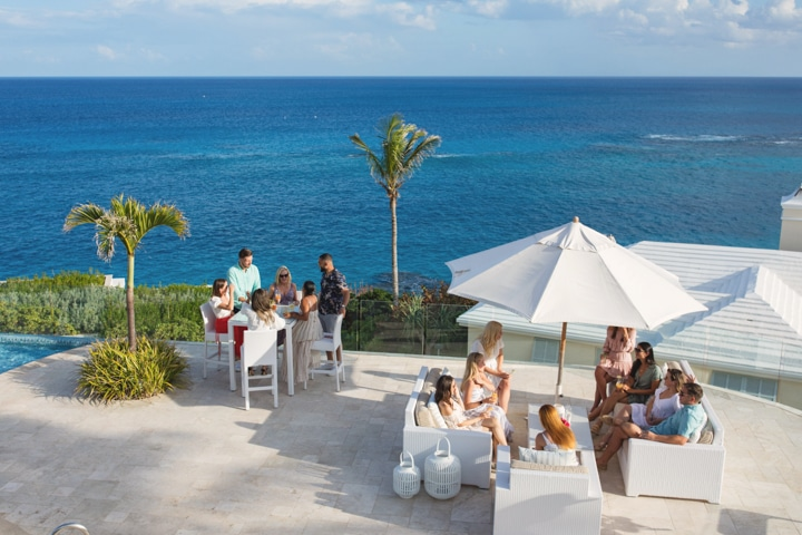 Groups of people at a dining area overlooking the ocean.