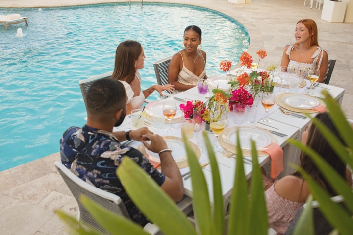 People seated at a poolside dining table.
