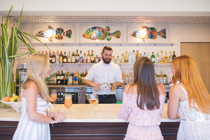 A bartender serving drinks to three people.