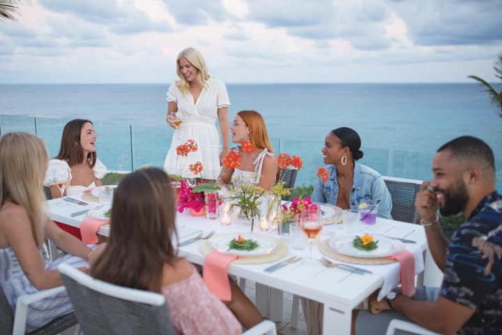 A group of people seated at a dining table outside, overlooking the ocean.