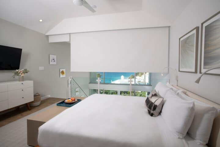 A loft bedroom with white shades covering a large window.