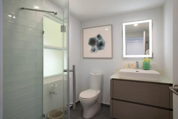 A bathroom with a toilet, sink, and lighted mirror.