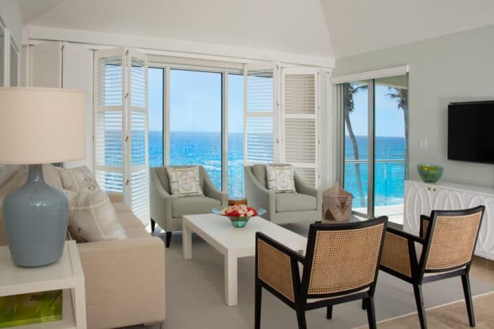 A living room with various seating alongside glass doors displaying an ocean view.