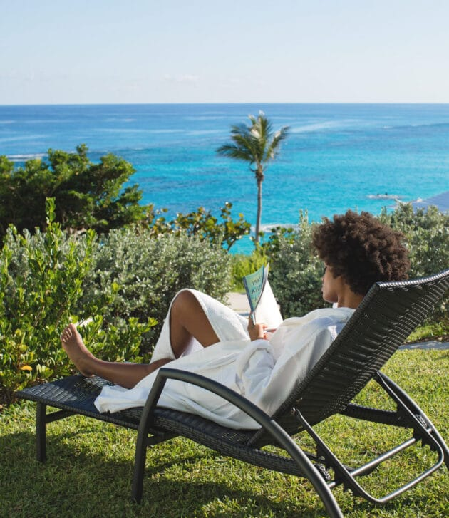 A woman relaxing in a lawn chair overlooking the ocean.