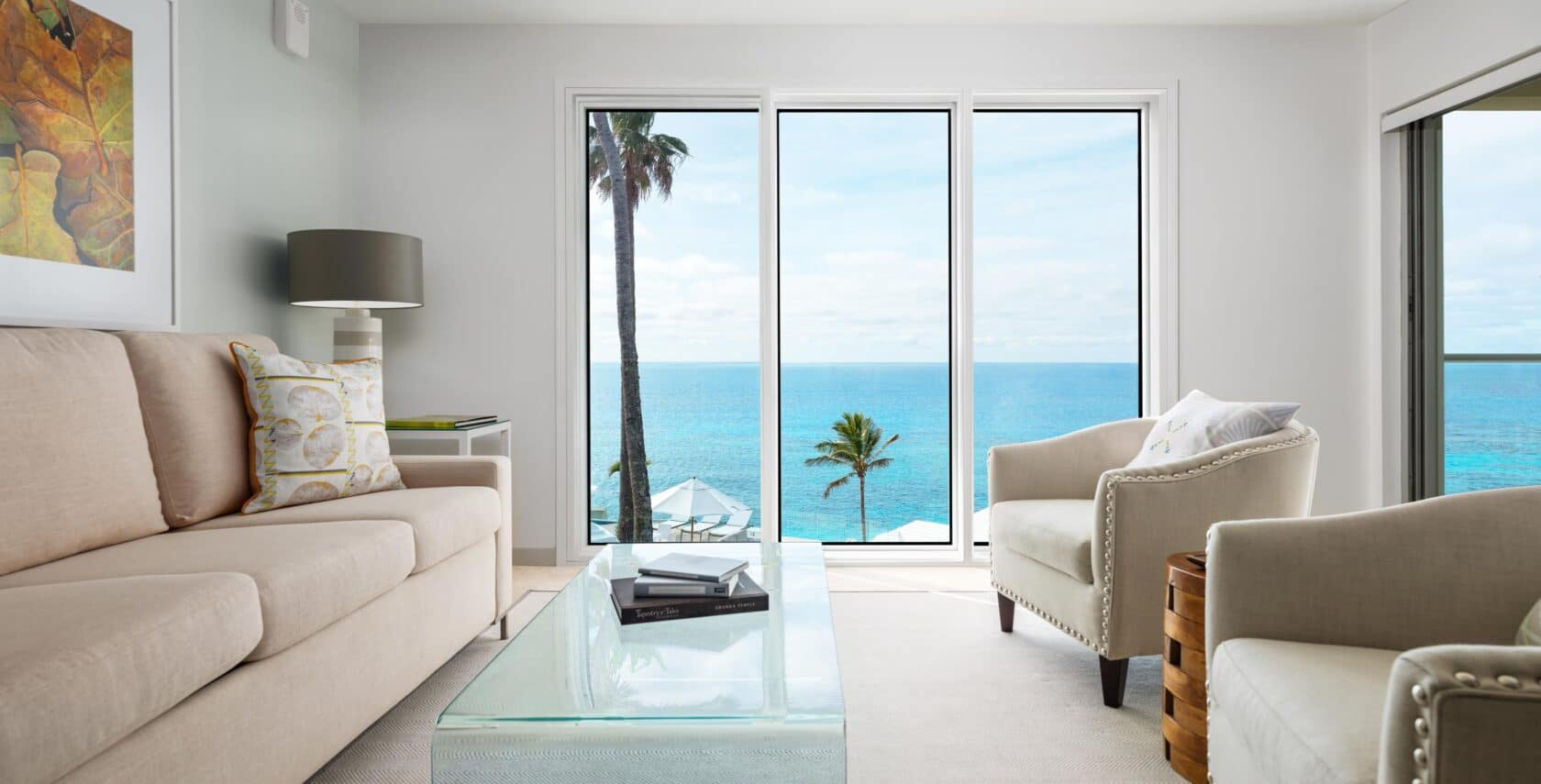 A living area with couches, a glass coffee table, and glass doors with an ocean view.