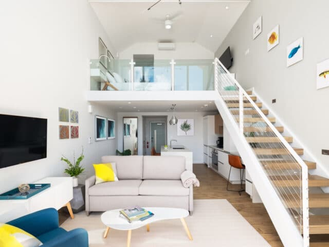 A living room with a staircase leading to a loft.