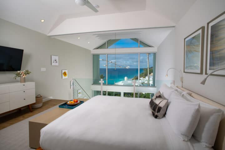 A loft bedroom with a TV and a large window with an ocean view.
