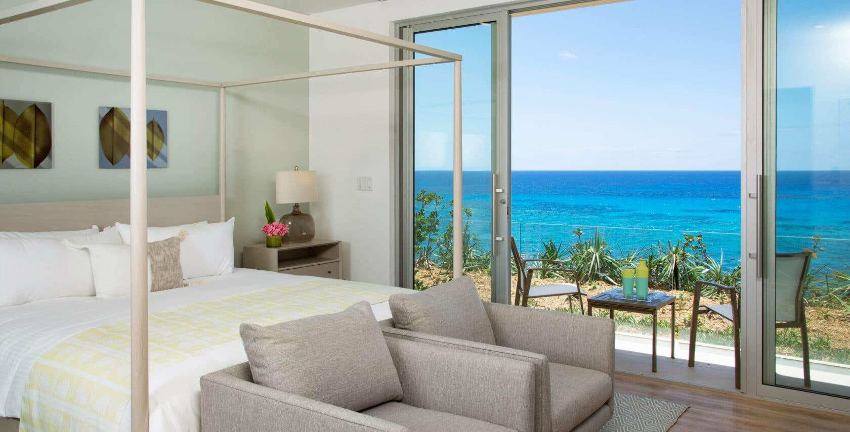 A bedroom with large sliding glass doors leading to a patio overlooking the ocean.