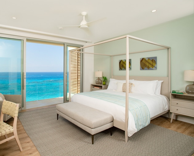 A bedroom with a canopy bed and large glass sliding doors displaying an ocean view.