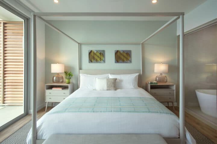 A canopy bed with white sheets and pillows.