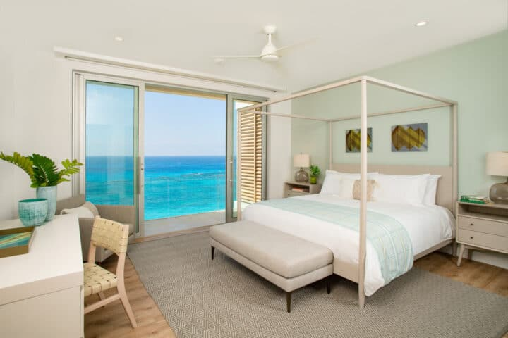 A bedroom with large glass doors with an oceanfront view.