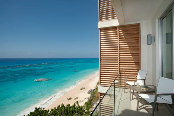 A balcony with two chairs overlooking a beach.