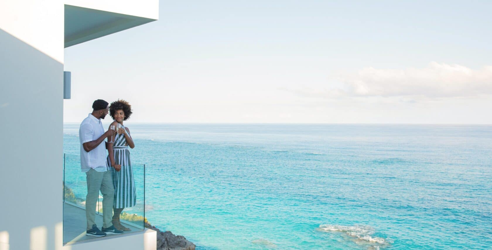 A couple on a balcony overlooking the ocean.