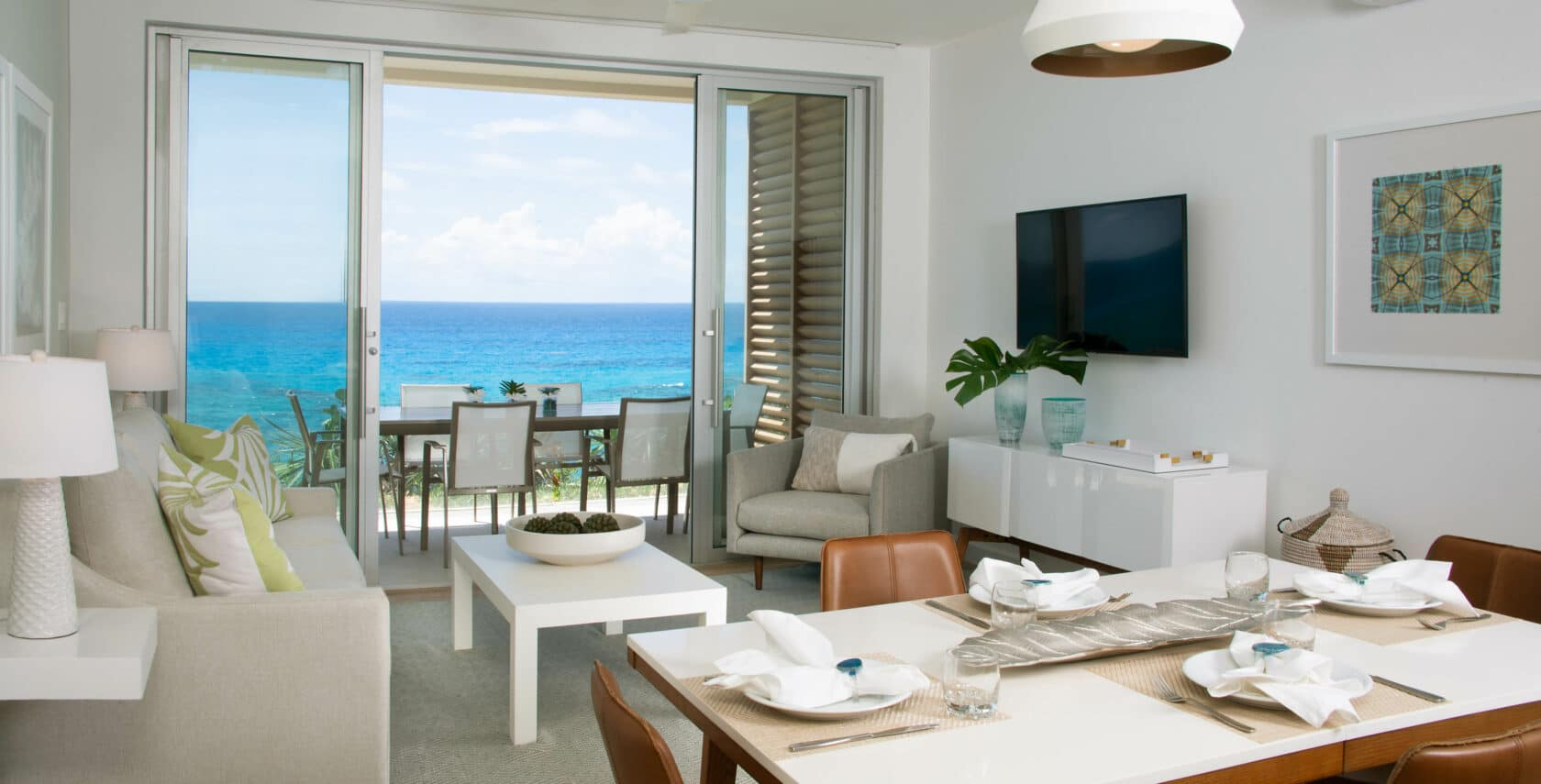 A living and dining area with large glass doors showing an oceanfront view.