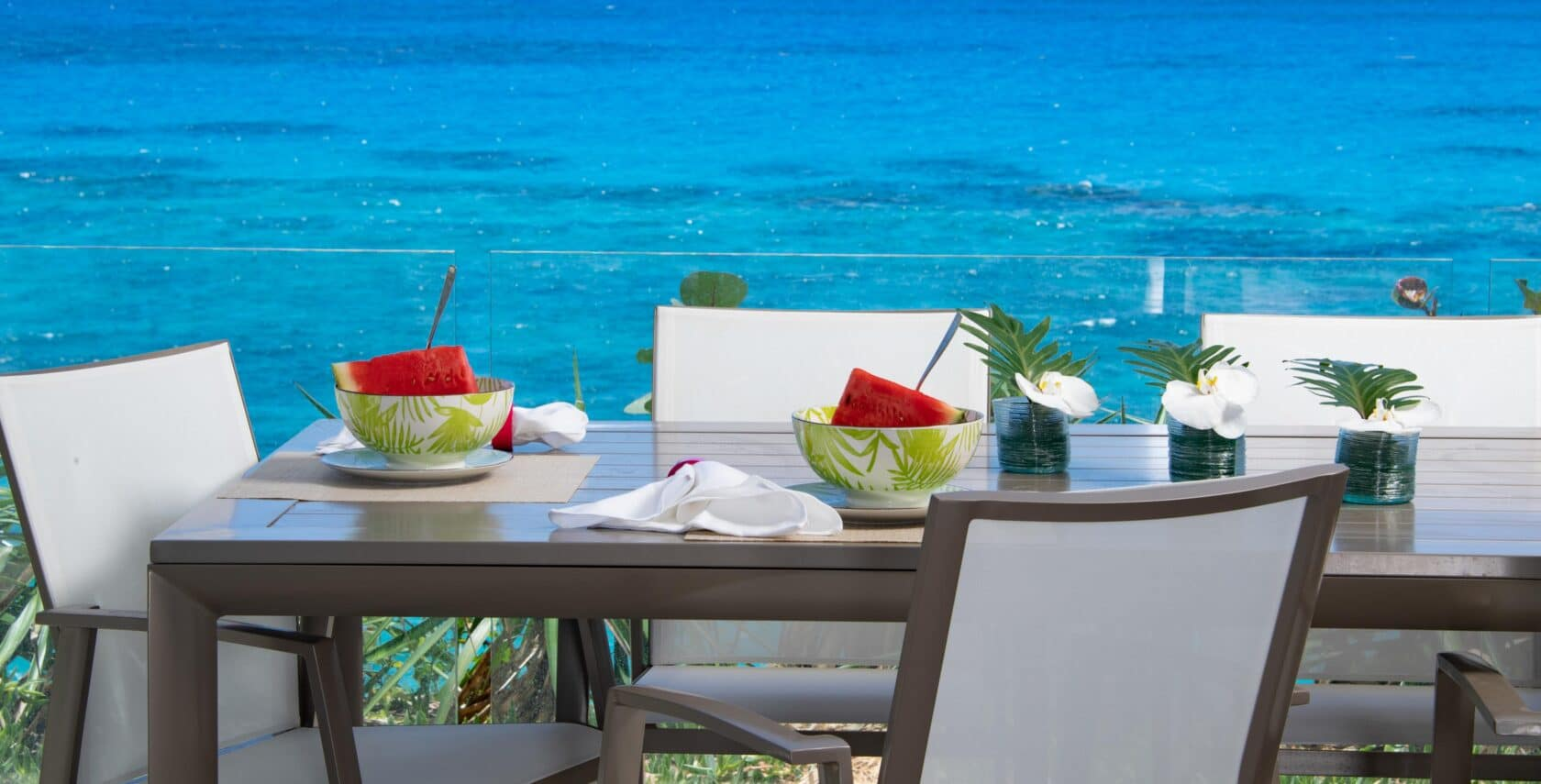 A dining table outside with a view of the ocean in the background.