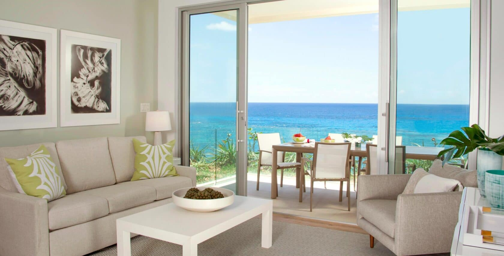 A living area with large glass doors leading to an outdoor dining area with an ocean view.