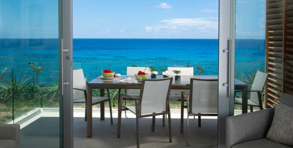 A patio with a dining table set with watermelon, with an ocean view in the background.