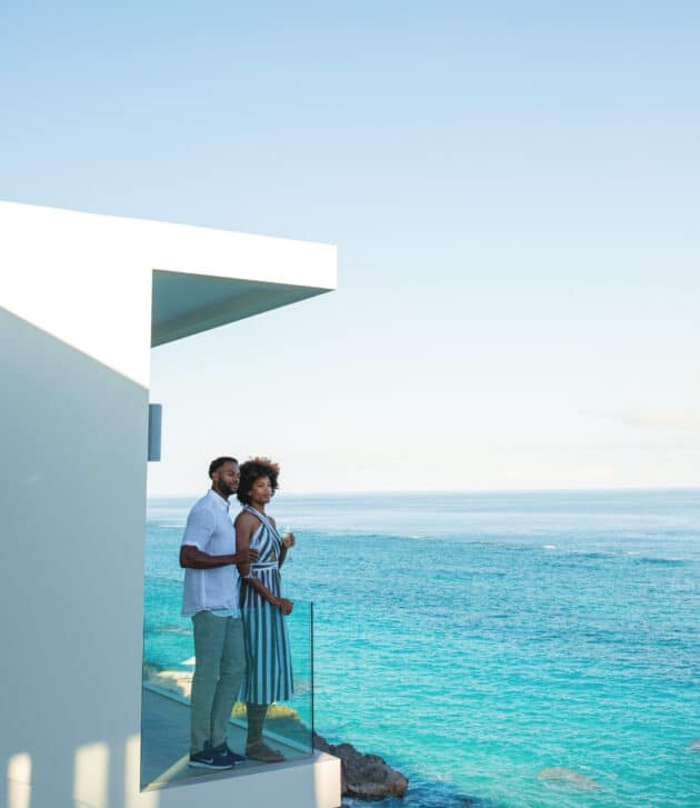 A couple standing together on a balcony overlooking the ocean.