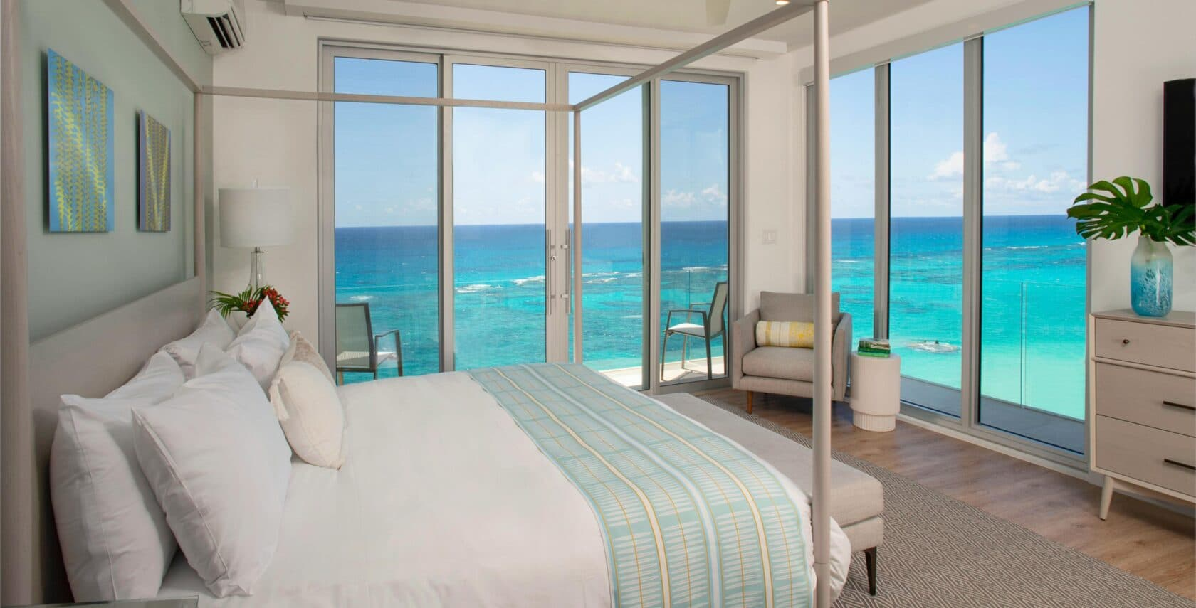 A bedroom with a canopy bed and large glass doors with an ocean view.