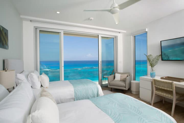 A bedroom with two beds, a desk, and glass sliding doors displaying an ocean view.