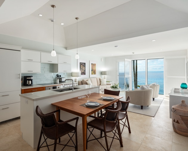 A kitchen and dining area with a living area in the background.