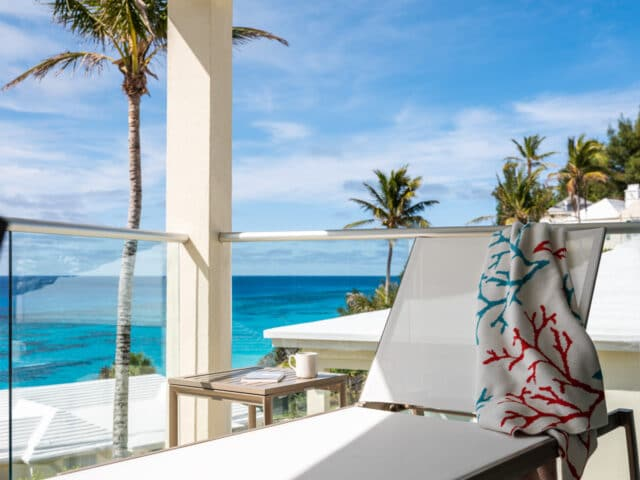 A lounge chair with a towel draped over it, with an ocean view in the background.