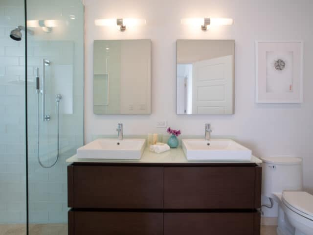 A bathroom with two sinks and two mirrors.