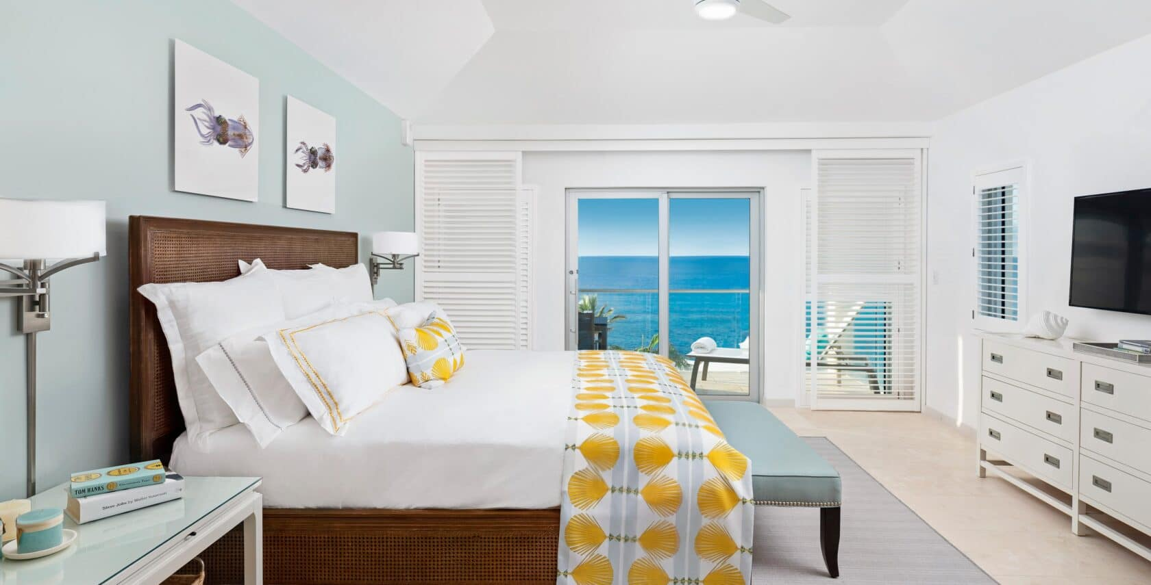 A bedroom with glass doors showing an ocean view.