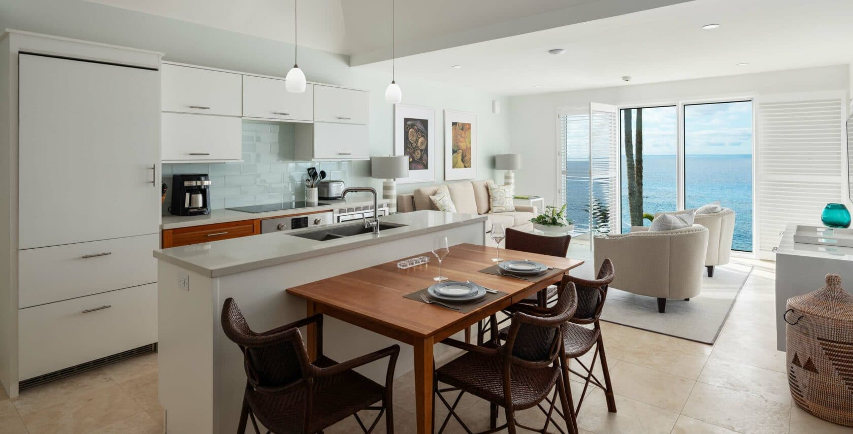 A kitchen area with white cabinets and a brown dining table.