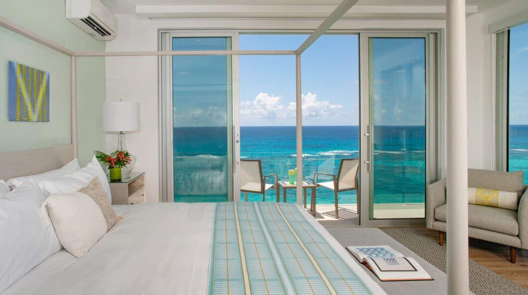 A bedroom with a canopy bed, and sliding glass doors leading to a deck overlooking the ocean.