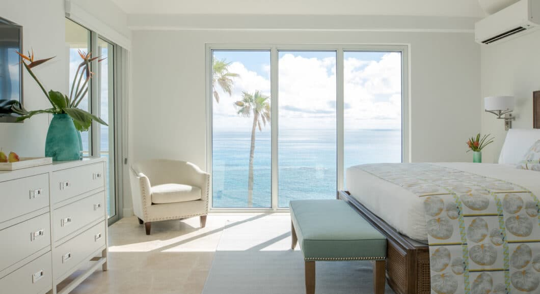 A white bedroom with sliding glass doors with a view of the ocean.