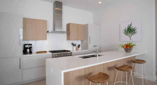 A kitchen area with white walls and wooden accents.