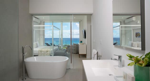 A bathroom connected to a bedroom with a sliding glass door in between.