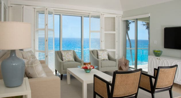 A living room with various chairs, and glass doors with a view of the ocean.