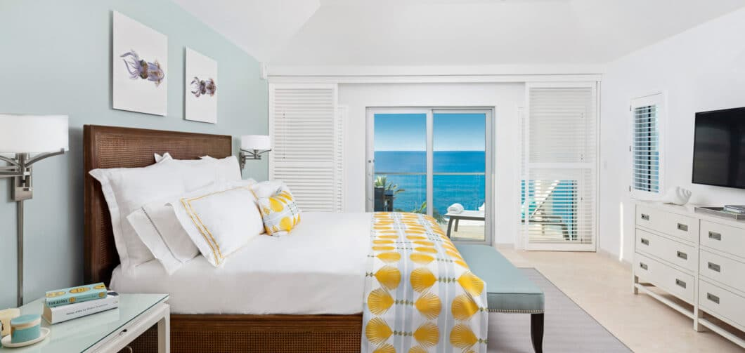 A bedroom with sliding glass doors showing a view of the ocean.