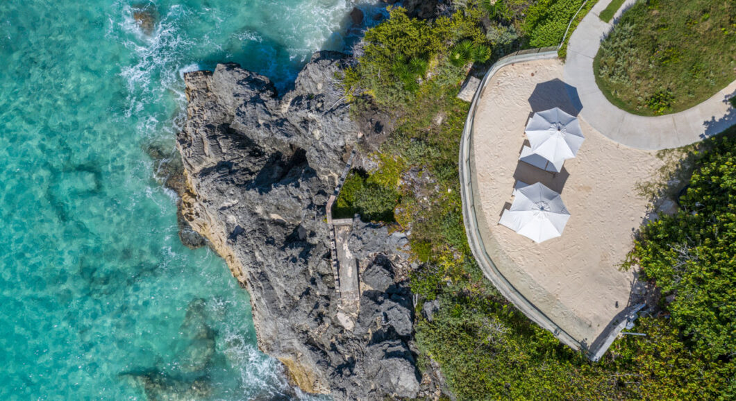 An aerial view of the ocean, rocks, and two parasols.