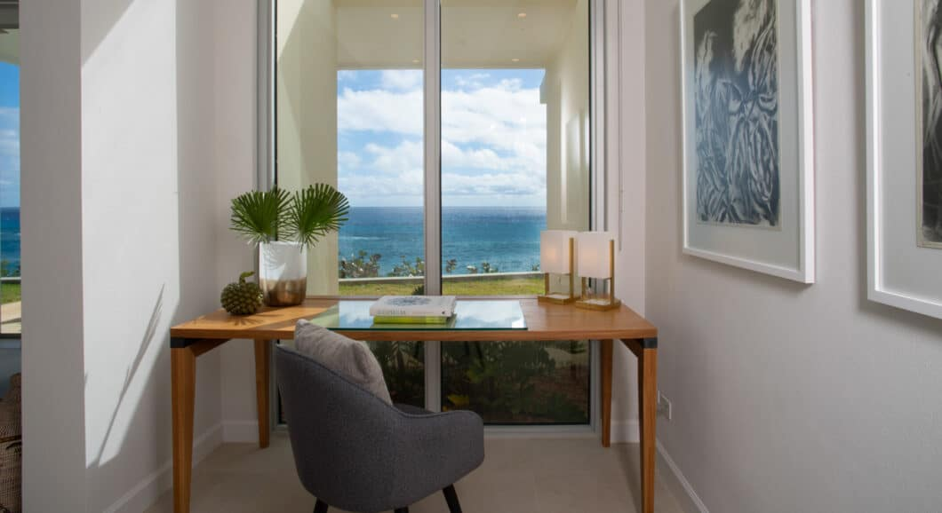 A desk in front of tall windows showing an ocean view.