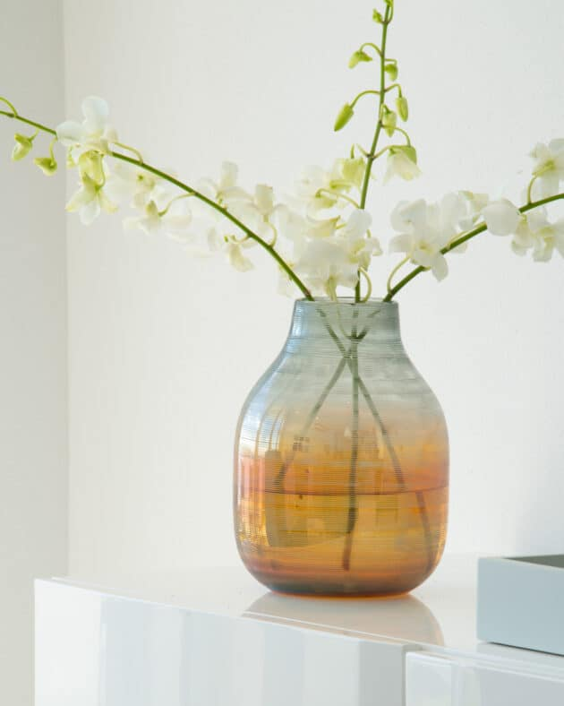 A vase with white orchids.