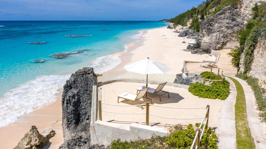 A terrace with a two beach chairs and a parasol, overlooking a beach.