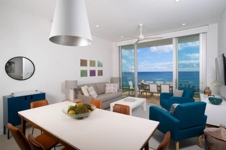 A living and dining area with large glass doors with an ocean view.