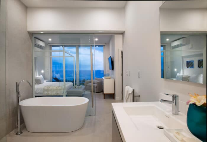 A bathroom connected to a bedroom with large glass doors.