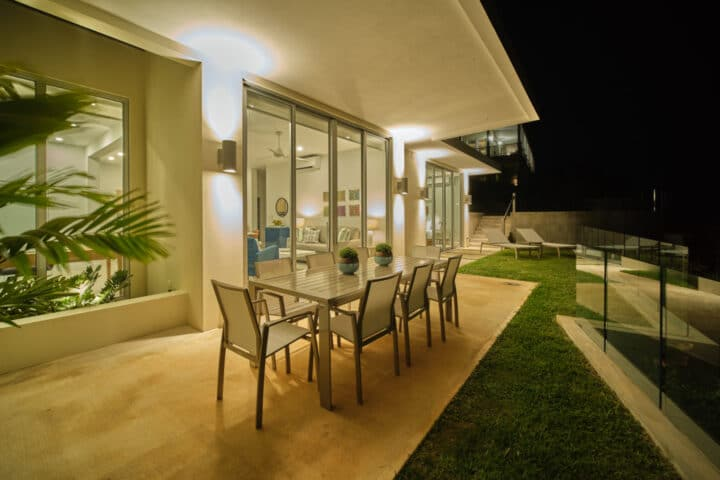 An outdoor deck at night with a table and chairs.