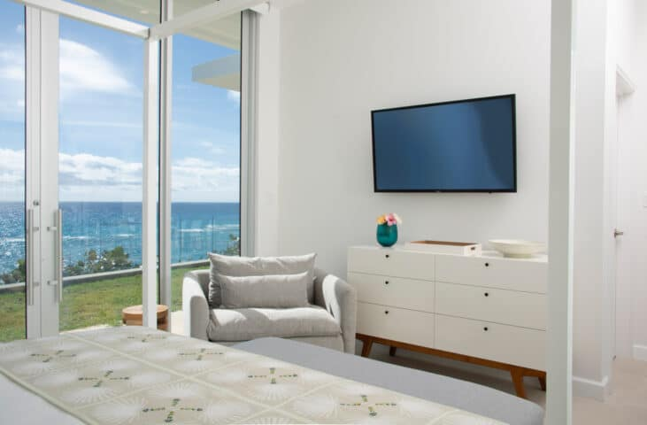 A bedroom with a dresser, chair, and TV on the wall, along with glass doors.