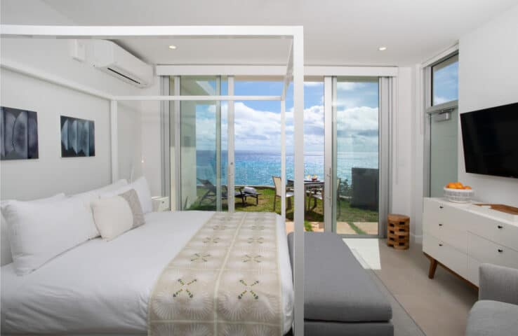 A bedroom with sliding glass doors leading to a patio overlooking the ocean.