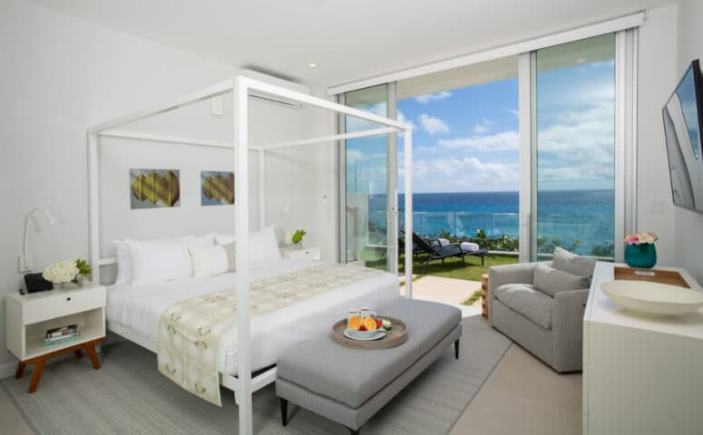 A bedroom with a canopy bed and sliding glass doors leading to a deck overlooking the ocean.