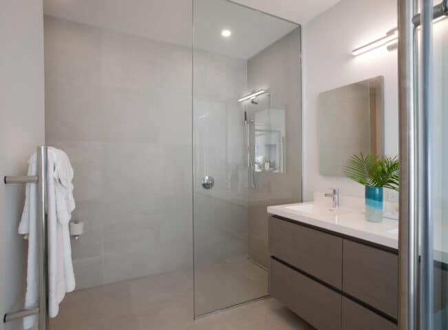 A bathroom with two sinks and a shower.