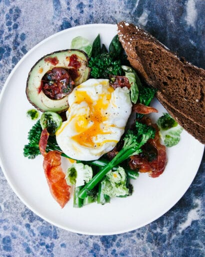 A dish with a poached egg, vegetables, and a slice of bread.